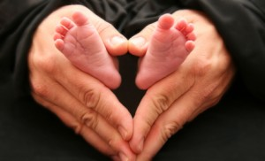 baby feet and adult hands